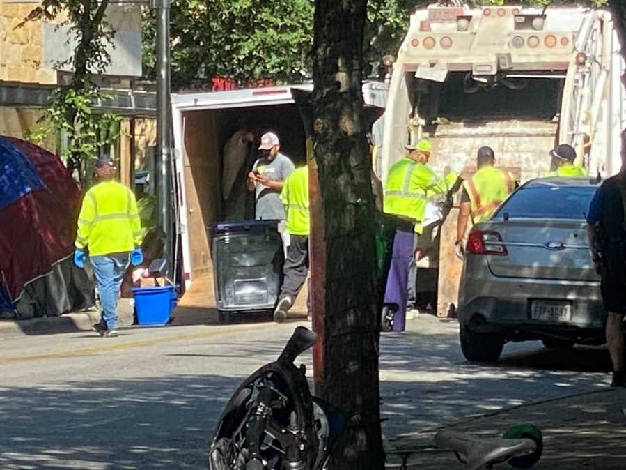 Austin police officers and other city employees are clearing out homeless encampments around City Hall on Monday. (KXAN photo/Todd Bynum)