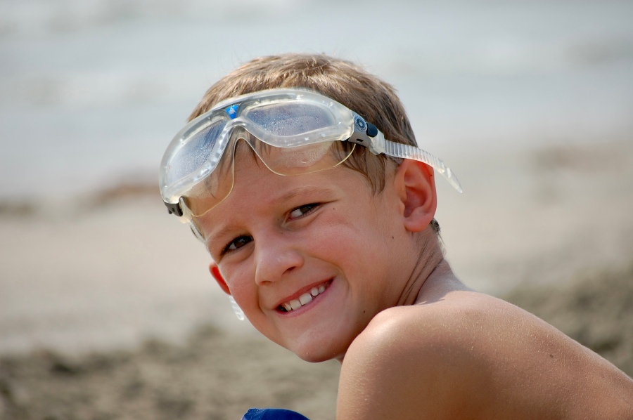 Cameron Stewart, wearing swimming goggles at about 11 years, smiles for a picture at the beach.