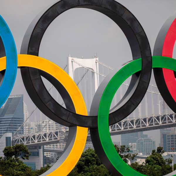 """The Rainbow Bridge is seen through a large size Olympic rings symbol at """"Tokyo Waterfront"""" in the waters of Odaiba Marine Park on August 6, 2020, while the display is transferred back to the factory where it was manufactured for a safety inspection and to receive maintenance. (Photo by Behrouz MEHRI / AFP) (Photo by BEHROUZ MEHRI/AFP via Getty Images)"""