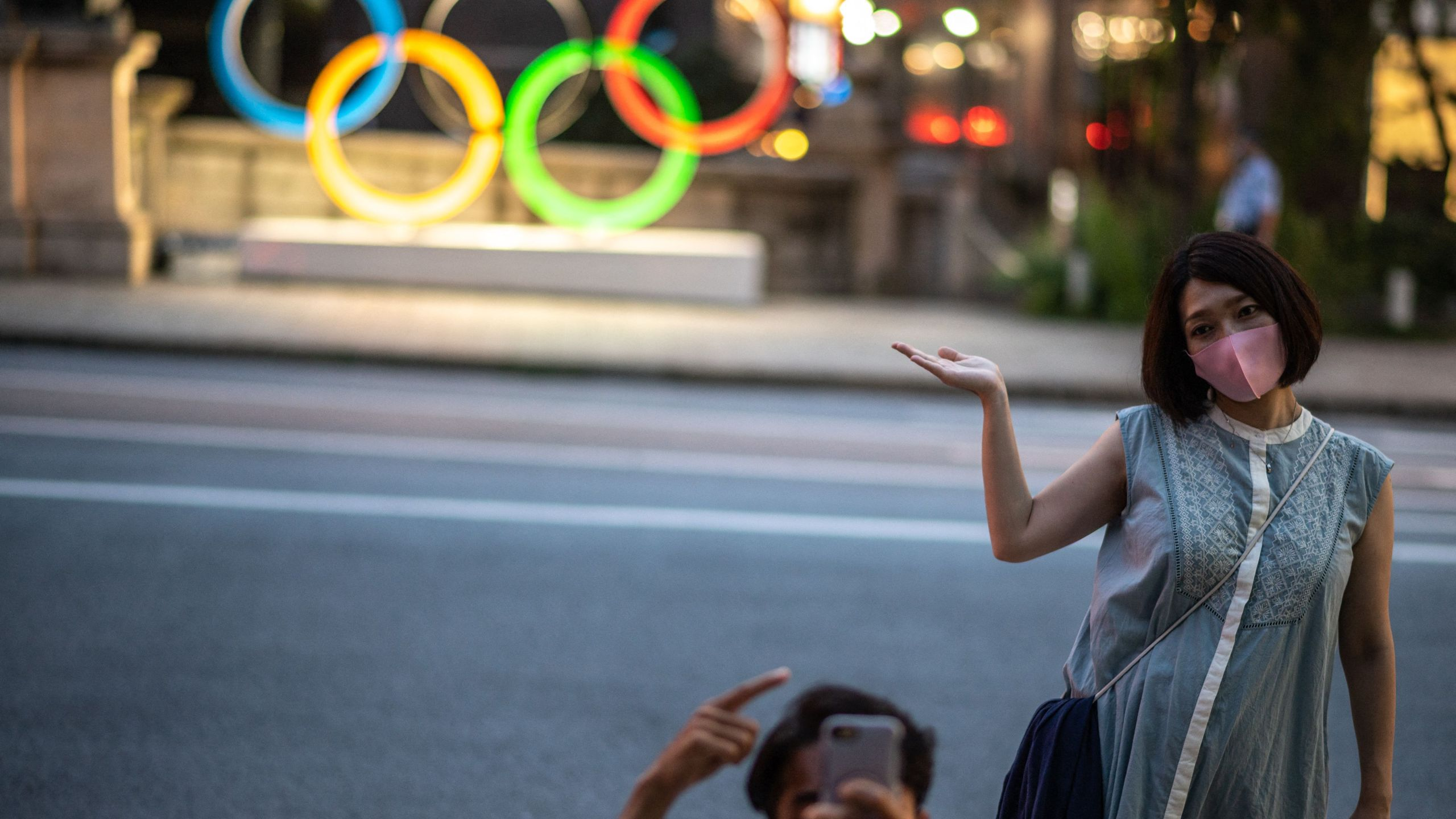 A couple pose in front of the Olympic Rings in Tokyo's Nihonbashi district on July 10, 2021. (Photo by Philip FONG / AFP) (Photo by PHILIP FONG/AFP via Getty Images)