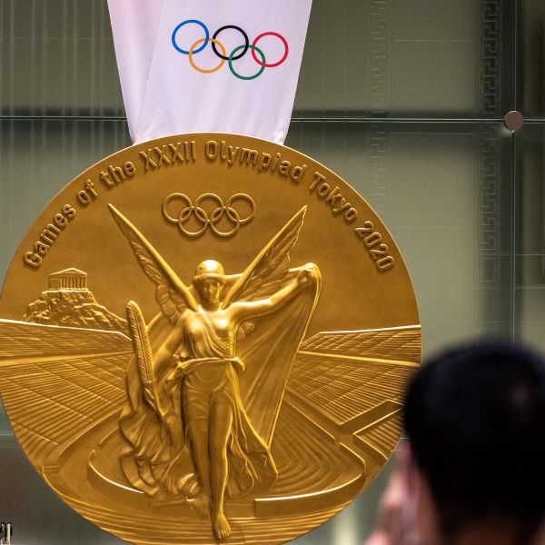 A man takes pictures of a large-scale reproduction of the Tokyo 2020 Olympic Games gold medal as part of the Olympic Agora event at Mitsui Tower in Tokyo on July 14, 2021. (Photo by Philip FONG / AFP) (Photo by PHILIP FONG/AFP via Getty Images)