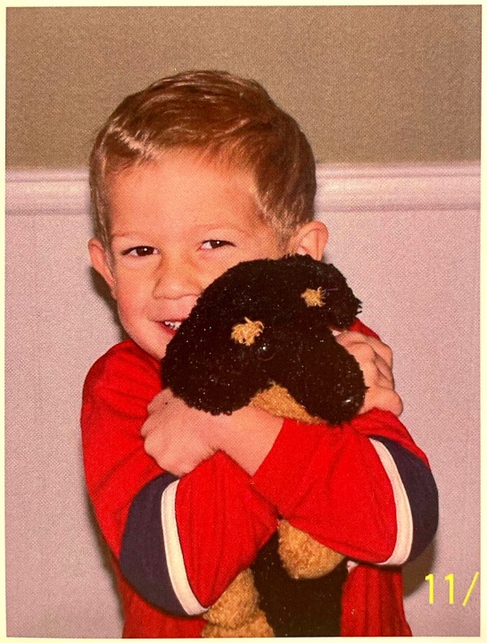 Cameron Stewart hugging his stuffed animal puppy as a young child