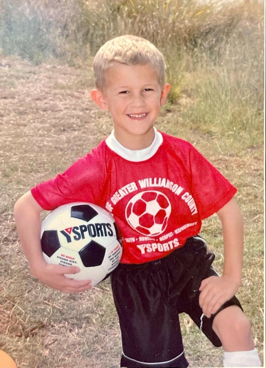 Cameron Stewart, roughly six years old, poses with a soccer ball under his arm for a photo during YMCA soccer practice.