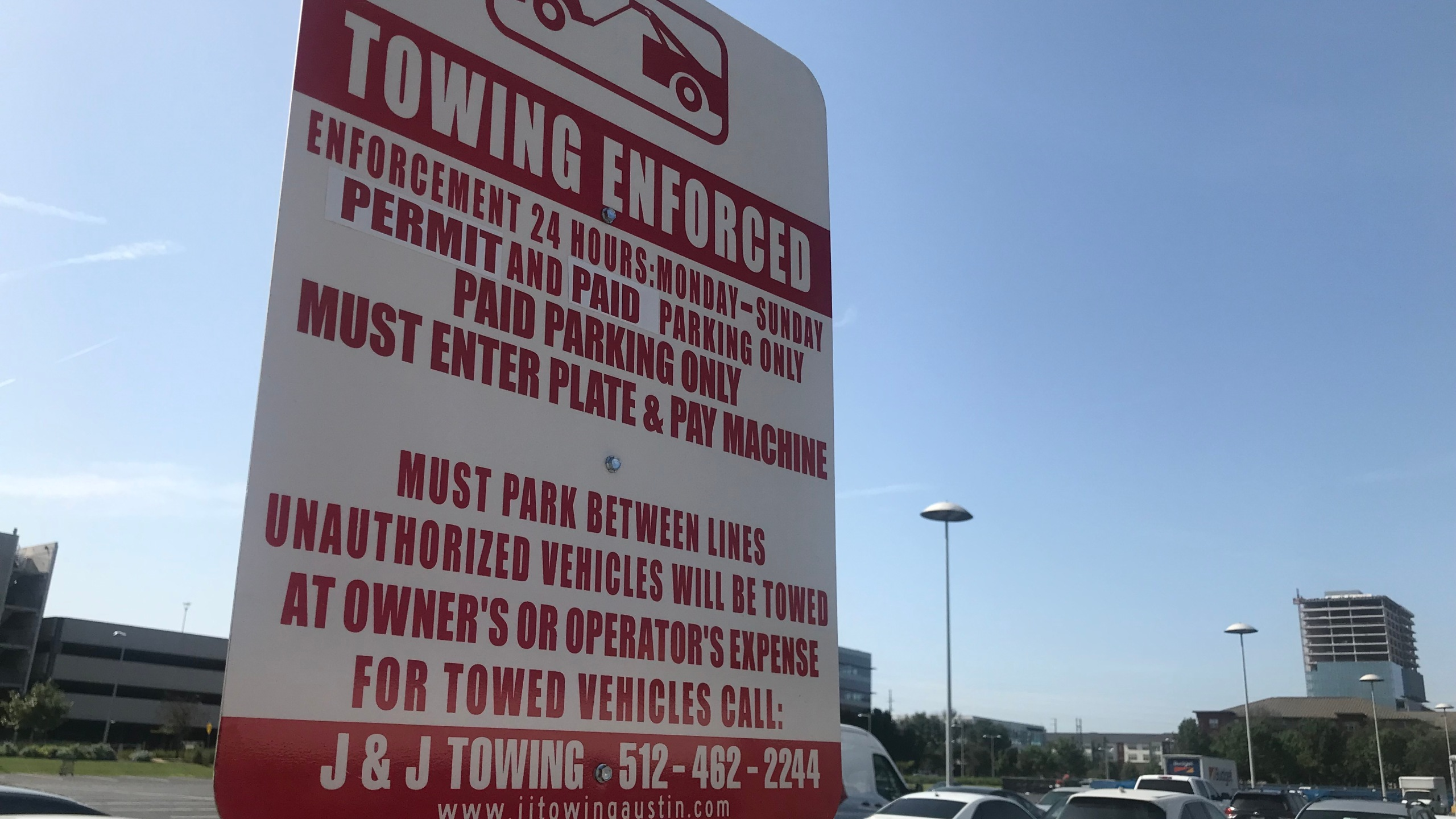 Towing signage and parking meters have popped up at a formerly free parking lot at the Domain -- and customers aren't happy about it. (KXAN Photo/Kelsey Thompson)