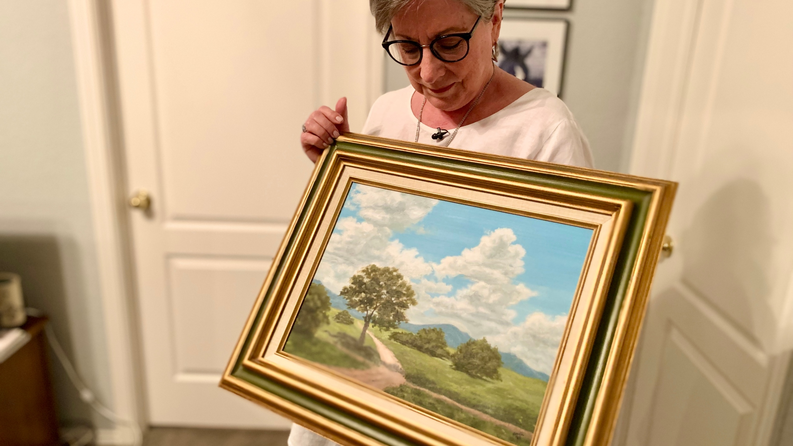 Sharon Butler's holds a painting her mother was working on when she had a stroke. It shows a landscape