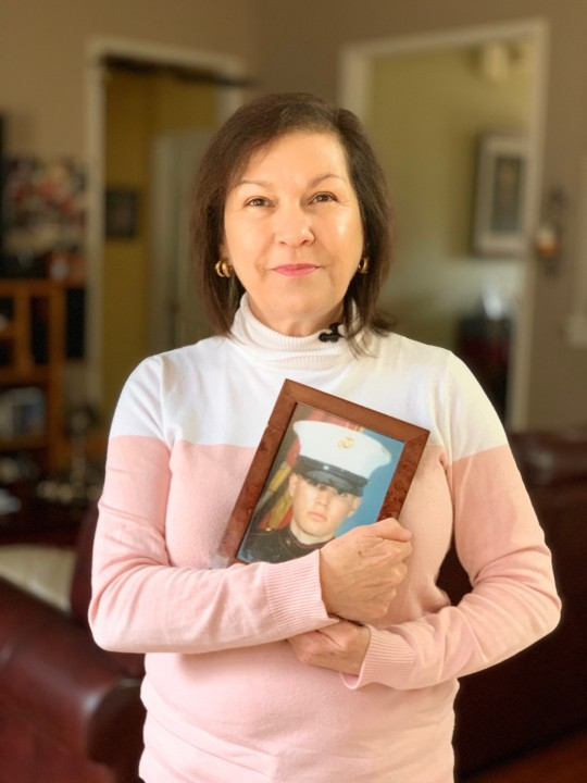 Maria Anna Esparza holds a framed picture of her son, Adan Castaneda, taken during his service in the Marines. Esparza has advocated for her son during his battles with mental illness and helped him navigate the state's criminal and mental health systems.