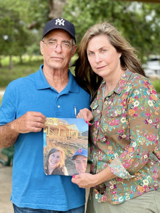 Meg Davis stands to the left of Tommy as they hold a photo of themselves in front of a home being constructed. She was three weeks from closing when her contract was canceled in Cedar Creek.