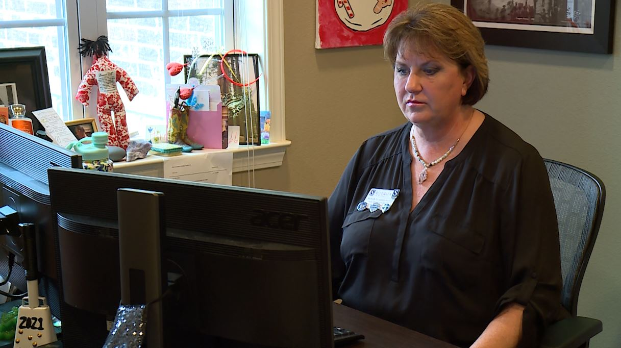 Michelle Neumann, the Senior Administrator Specialist at Silverado Barton Springs, sits in front of a computer and explains the added requirements and training necessary to stay certified in Texas for Alzheimer's care. (KXAN Photo/ Ben Friberg)