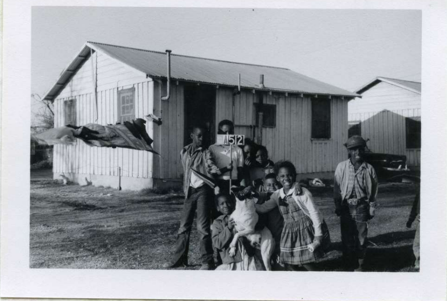 Nine kids and a dog stand in front of the rear view of a one-story house at 2351 Washington St. According to a written report, Clarence Flournoy owned parcel A-52 and Janie Alexander was the tenant of the home built around 1949. The appraised value of all 23 houses was $51,500. (Courtesy Austin History Center)