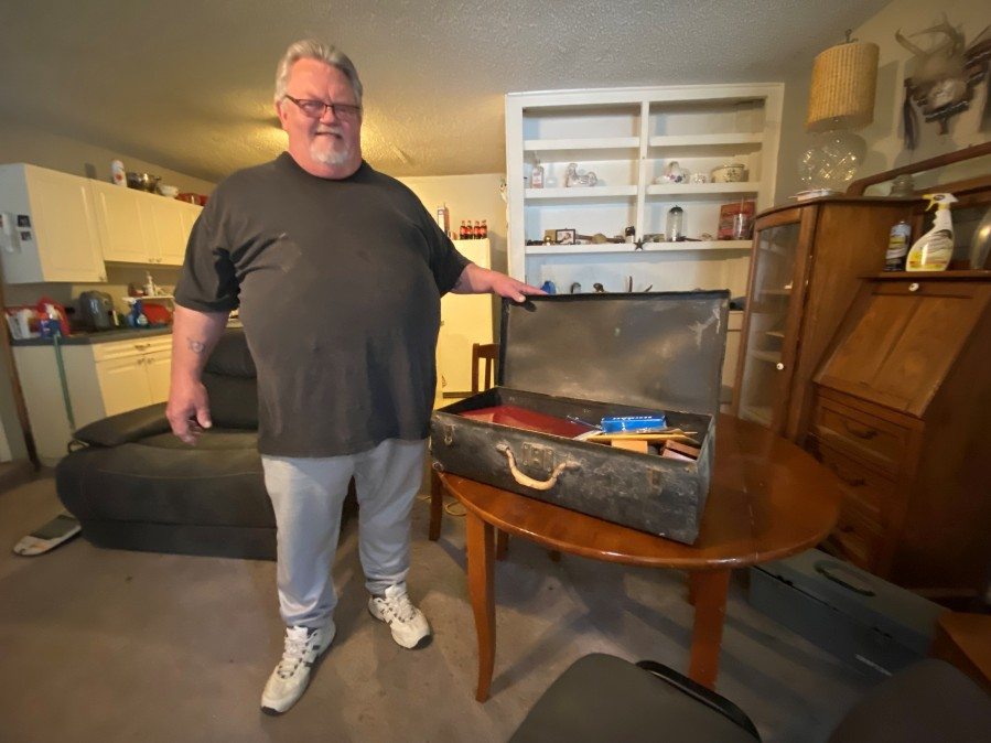 Man poses with drawer of antiques