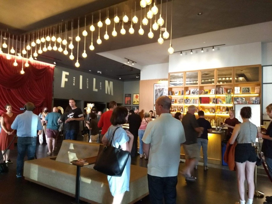 People gather by the bar at the cinema