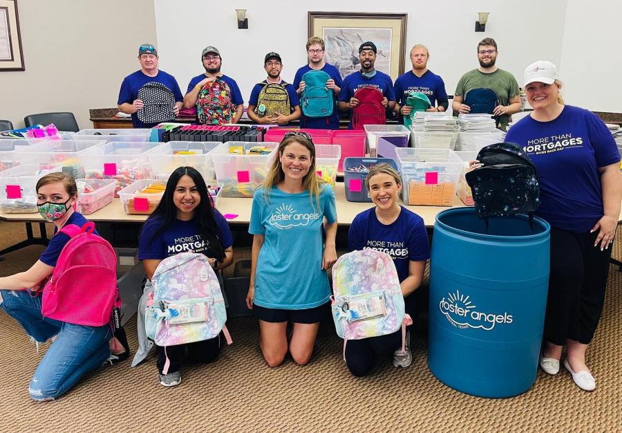 Volunteers pose with donated backpacks