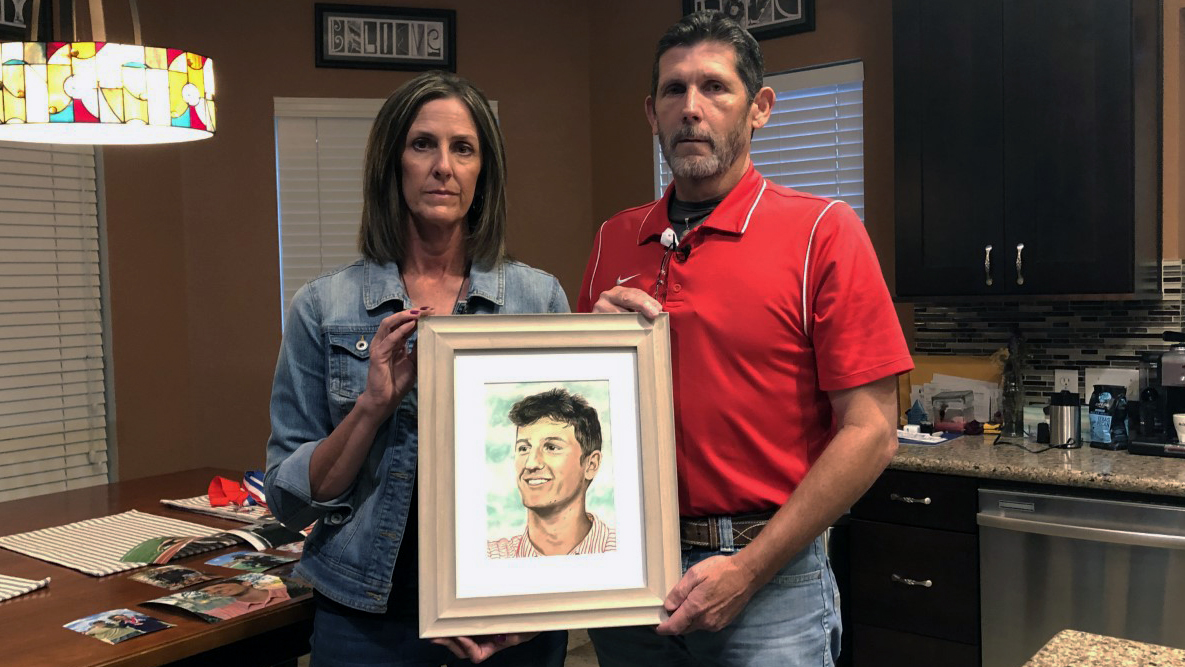 Becky and Dwayne Stewart stand in their kitchen holding a picture of their son, Cameron, who took a pill laced with fentanyl and died in March 2021. (KXAN Photo/Arezow Doost)