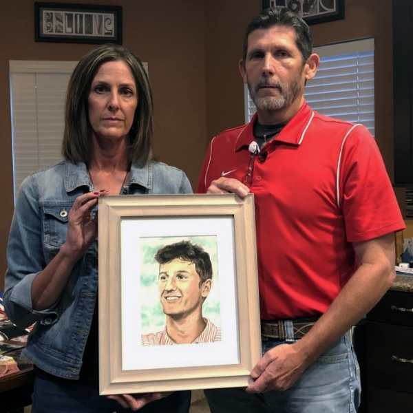 Dwayne and Becky Stewart hold a picture of their son, Cameron, who took a pill laced with fentanyl and died in March 2021. (KXAN Photo/Arezow Doost)
