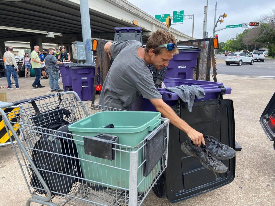 Evan Maddemma packs his belongings into a bin provided by the City of Austin (Grace Reader, KXAN)