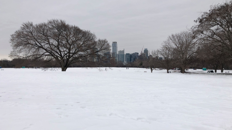 A photo of an Austin park covered in snow with downtown in the distance