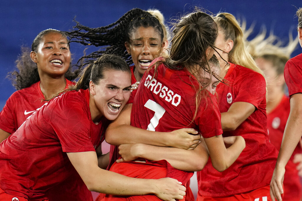 Teammates embrace Canada's Julia Grosso after she scored the winning goal against Sweden in the women's soccer match for the gold medal at the 2020 Summer Olympics, Friday, Aug. 6, 2021, in Yokohama, Japan. (AP Photo/Fernando Vergara)
