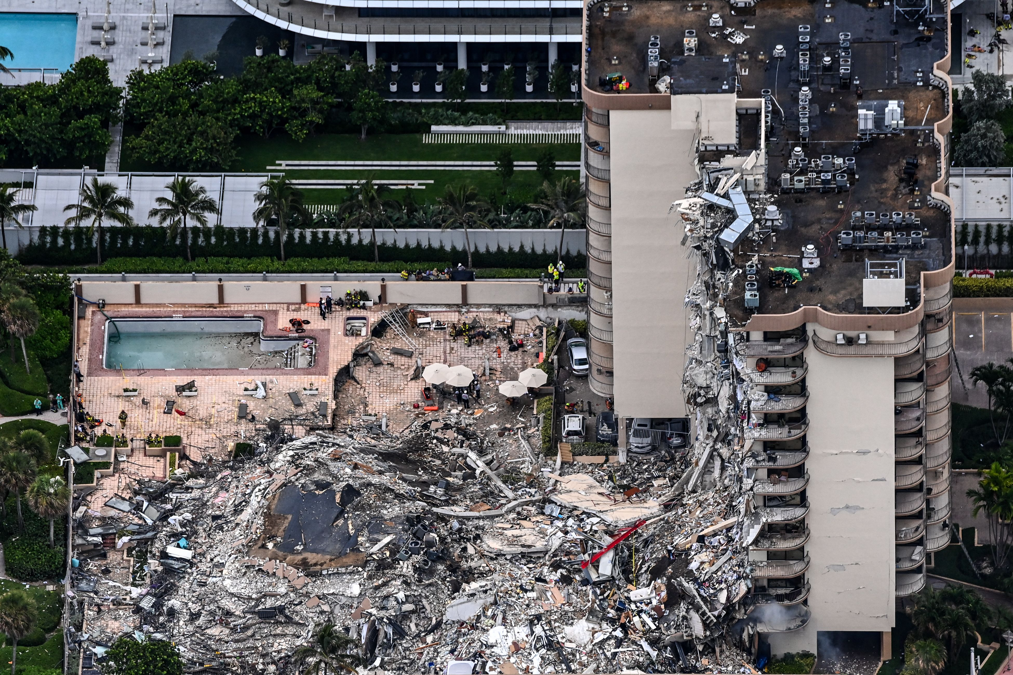 This aerial view shows search and rescue personnel working on site after the partial collapse of the Champlain Towers South in Surfside, north of Miami Beach, on June 24, 2021. (Photo by CHANDAN KHANNA/AFP via Getty Images)