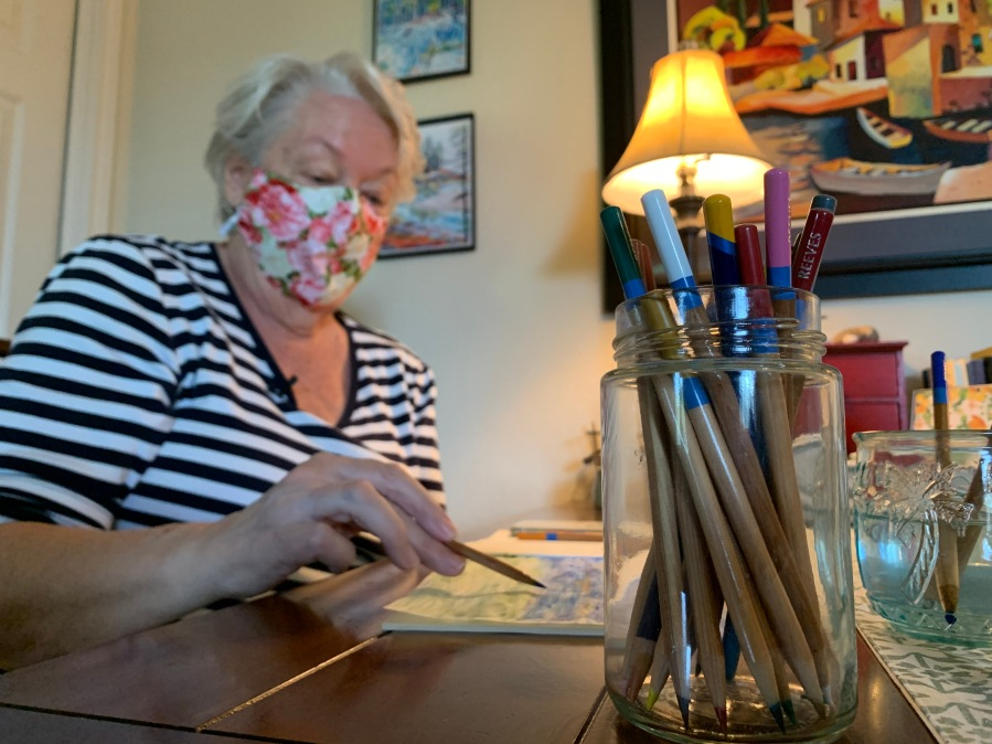 Linda Lee sits at her desk and works on an art project
