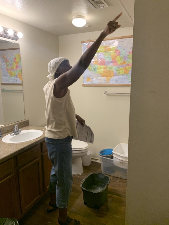 Dina Jo Thomas shows where water is leaking through her ceiling at her southeast Austin apartment. (KXAN Photo/ Avery Travis)