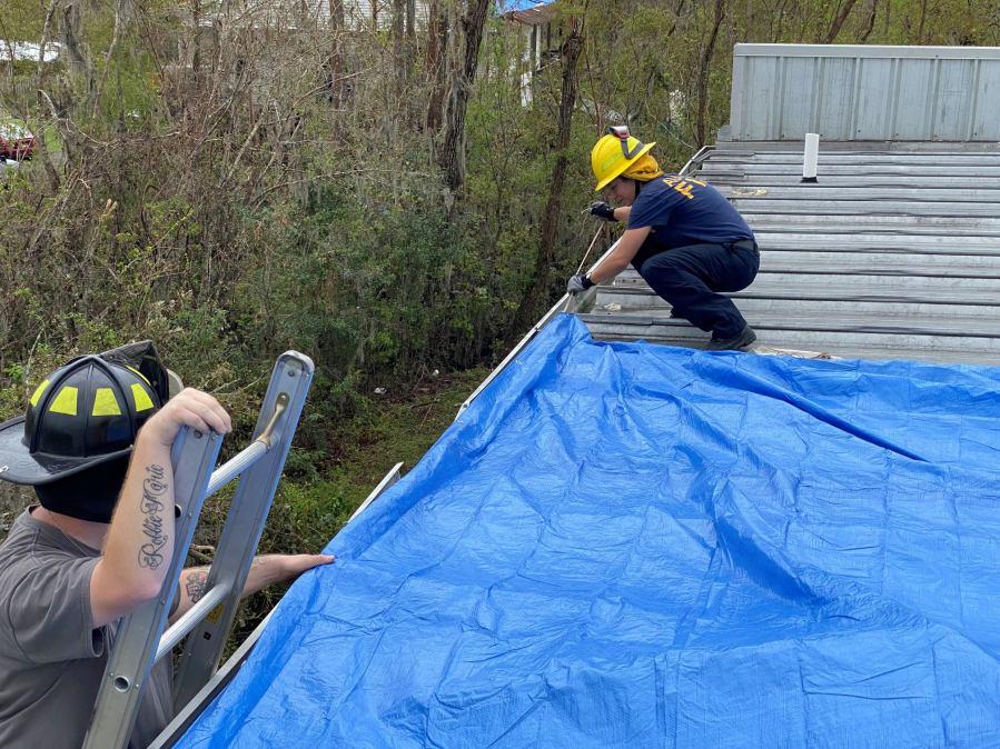 Fire Specialist Kim Ehardt placing tarps on the roof of a St John's Parish volunteer fire station in Pleasure Bend. (Photo credit: Lt. Jason Rudloff/Austin Fire Department)