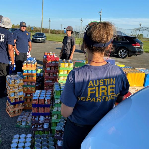 Group discussion on how best to divide up the food for the families in need and control the traffic. (Photo credit: Lt. Jason Rudloff/Austin Fire Department)