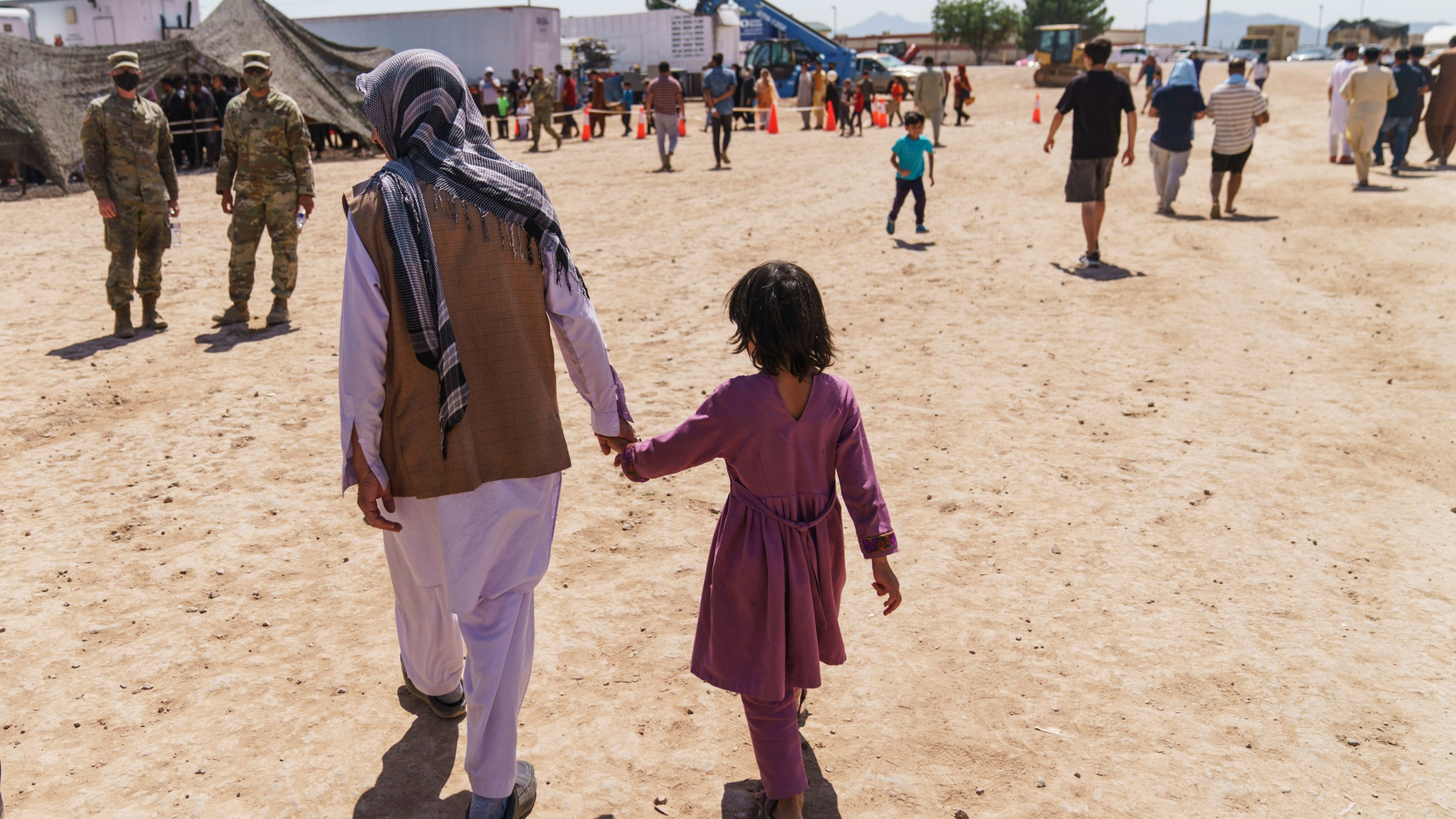 A man walks with a child through Fort Bliss' Doña Ana Village where Afghan refugees are being housed, Friday, Sept. 10, 2021. The Biden administration provided the first public look inside the U.S. military base where Afghans airlifted out of Afghanistan are screened, amid questions about how the government is caring for the refugees and vetting them. (AP Photo/David Goldman)
