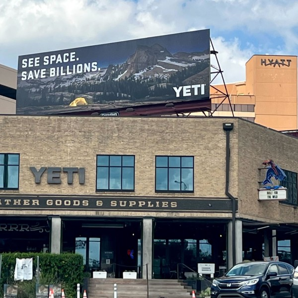 """YETI posted a bright new billboard outside its downtown Austin storefront. The message sends waves reading — """"See Space. Save Billions."""" (KXAN Photo/Ricky Garcia)"""