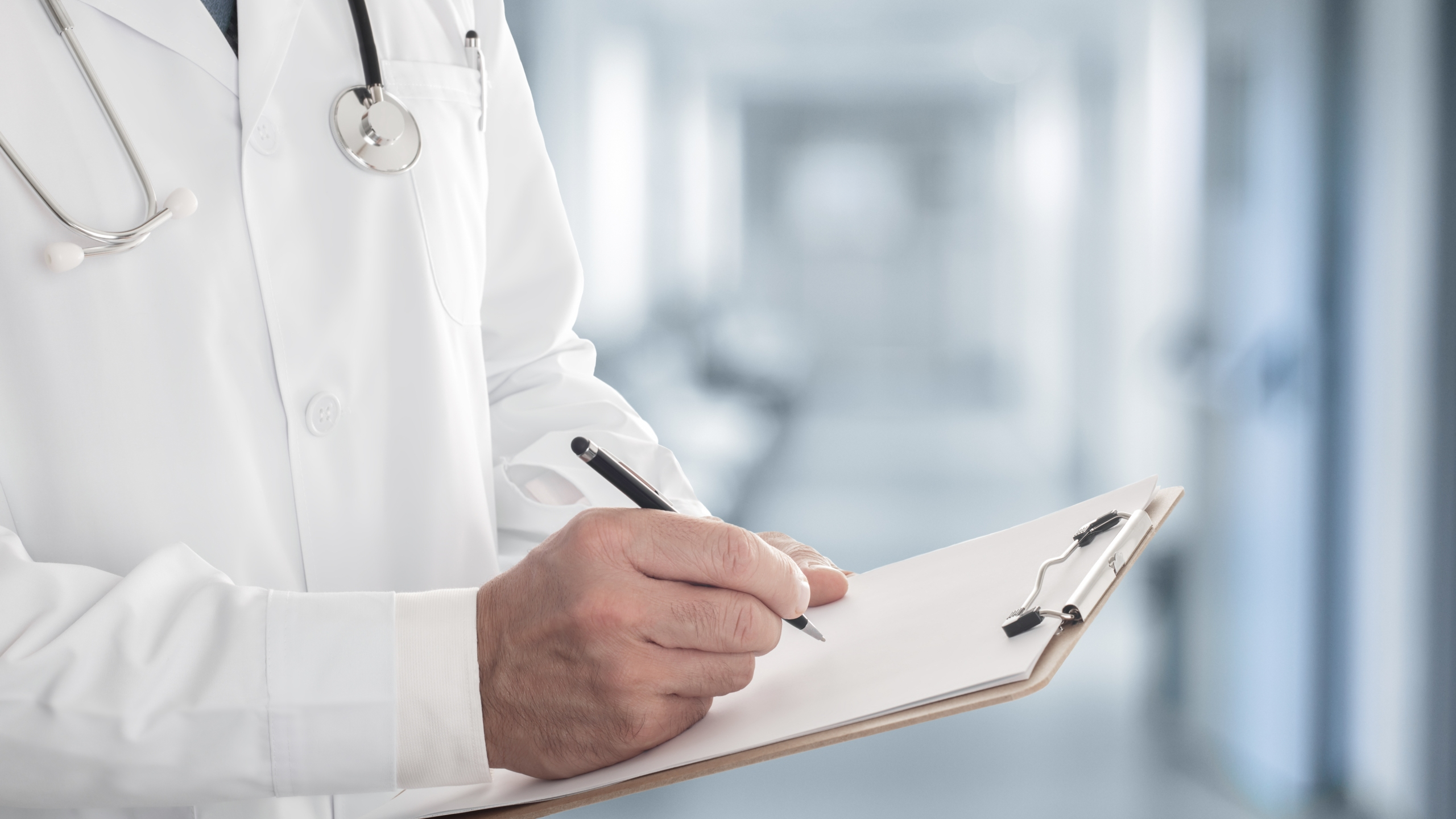 FILE photo of male doctor in white coat writing on a clipboard