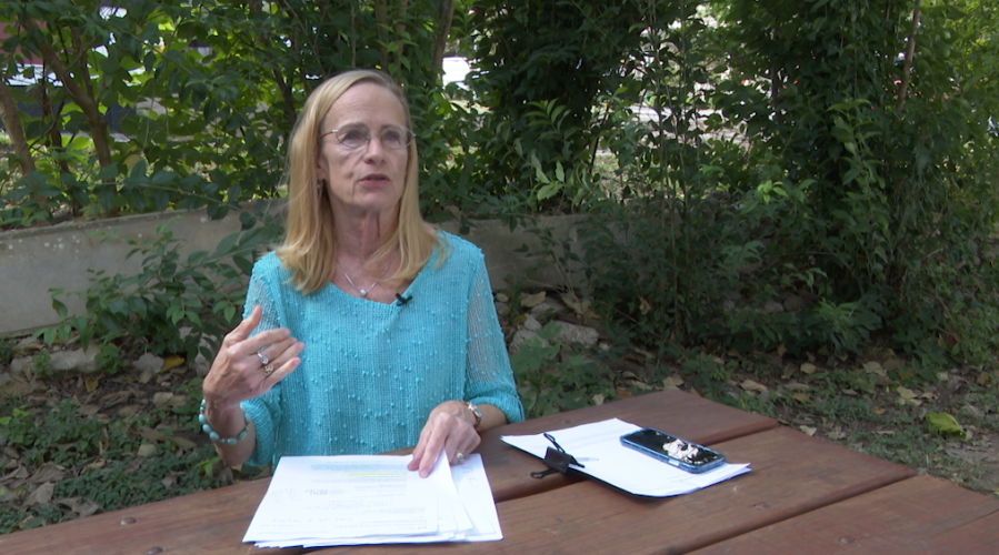 Real estate agent and property manager Mary Jo Schoppa speaks outside at a park bench with KXAN about her struggles with the Texas Rent Relief Program
