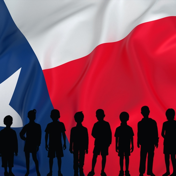 silhouettes of children in front of a large Texas flag