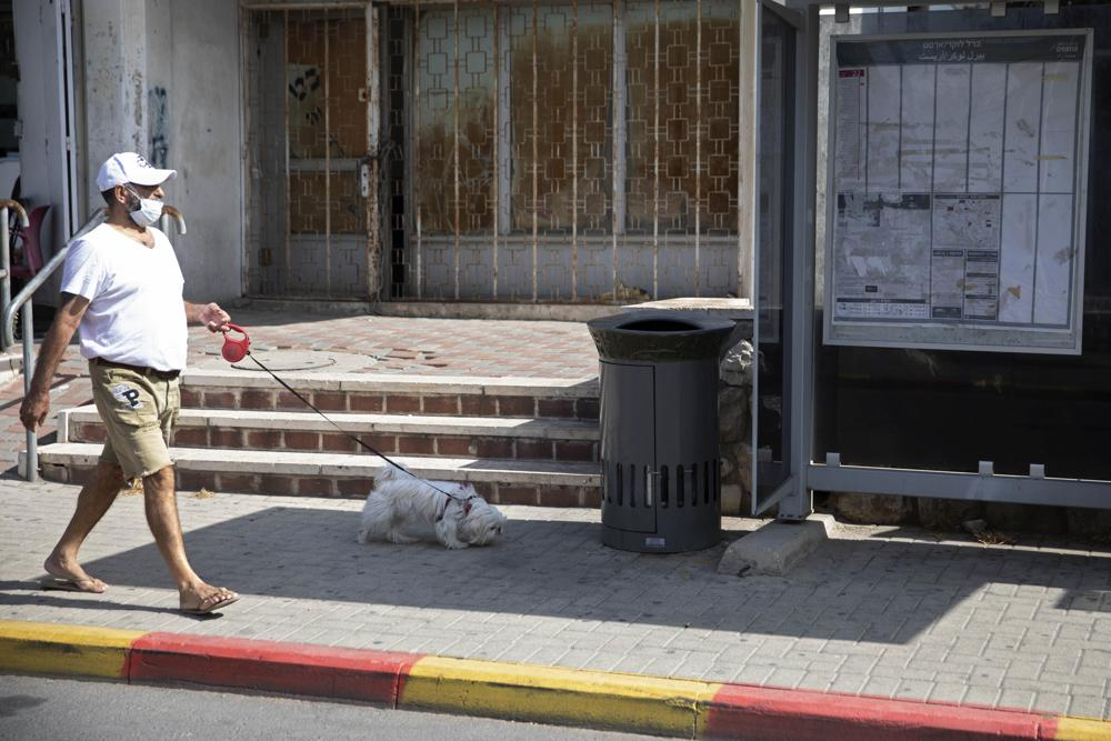"""An Israeli man walks a dog near a trashcan installed next to a bus stop that applauds to those who use it, in Jerusalem, Thursday, Oct. 14, 2021. Drop a piece of trash in, and a recording of a child's voice says """"Thank you very much!"""". (AP Photo/Sebastian Scheiner)"""