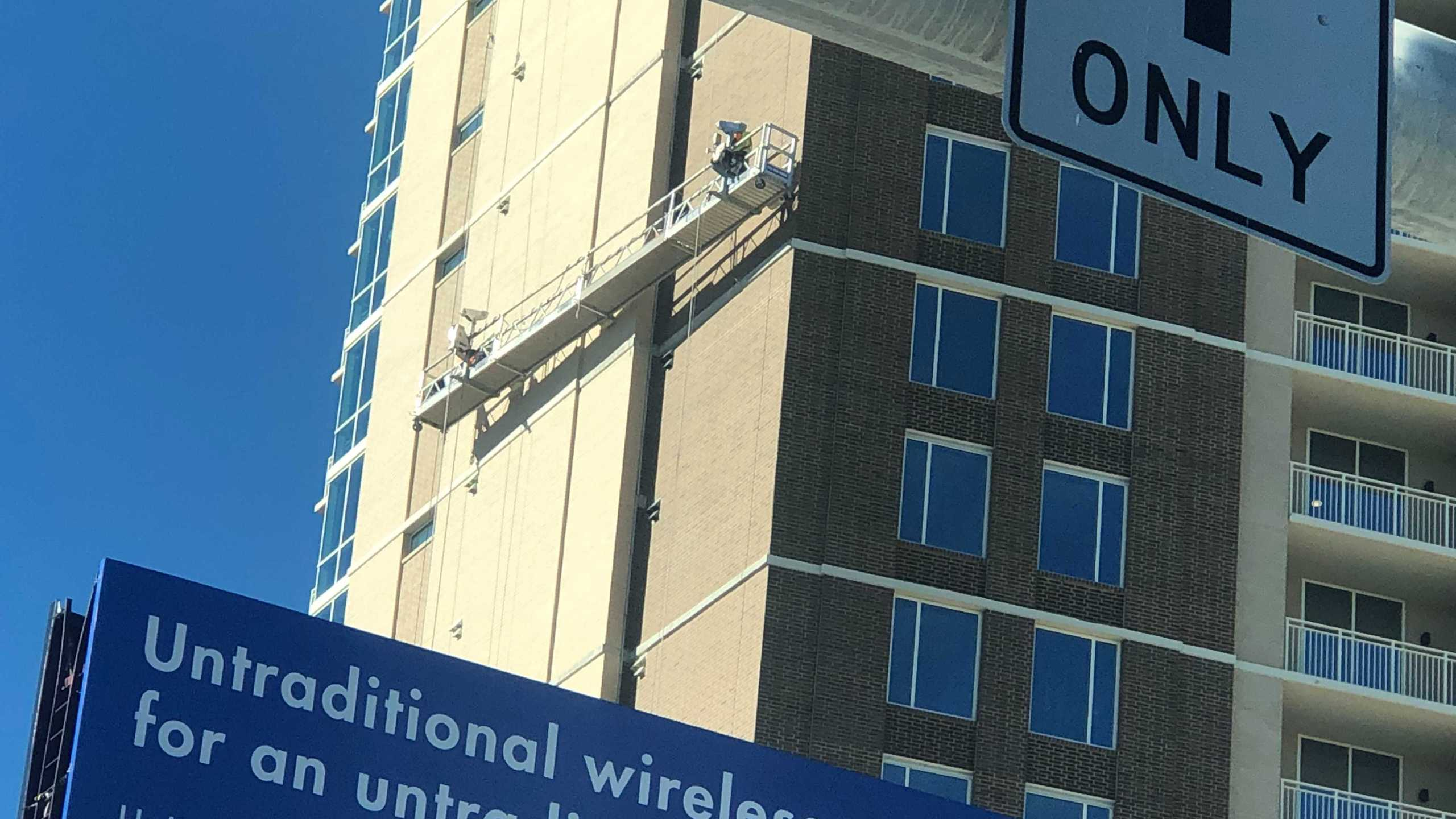 """A """"scaffolding malfunction"""" at a construction site left 2 people """"hanging from ropes"""" near I-35 and East 12 Street, ATCEMS said Thursday. (KXAN photo/Ed Zavala)"""