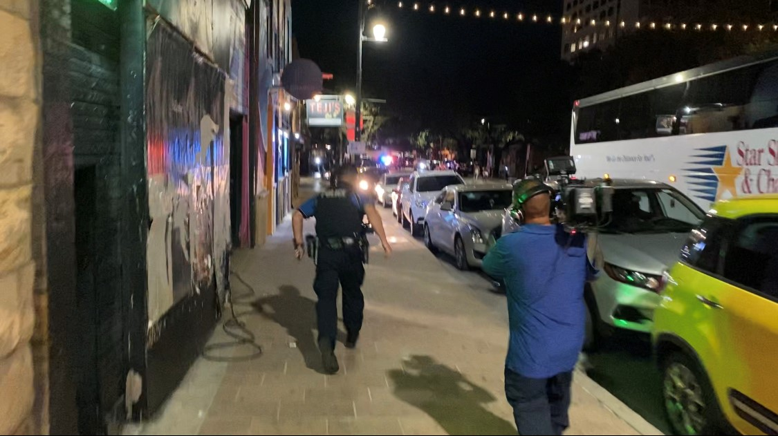 Sgt. Al Garibay of the Austin Police Department runs toward the scene of Saturday's early morning shooting, with a KXAN photographer behind (KXAN Photo/Kevin Clark)