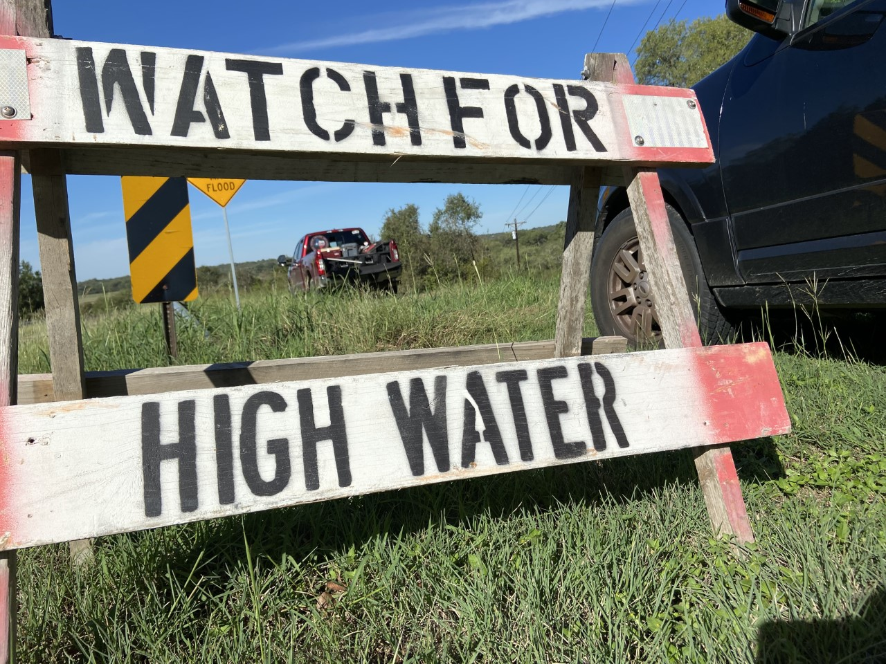 Watch for high water sign in front of search and rescue trucks